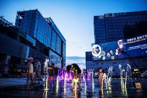 """夜幕降临,杭州的融小镇的广场开始热闹起来,家长带着小孩在喷泉下嬉戏。对于""""互之都""""的杭州成为爆雷的重灾区他们一无所知。"""