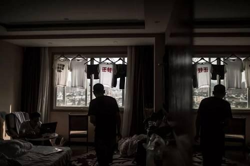 """酒店里挂着一件印有""""还钱""""两字的t恤,全国各地的难友制作了200件衣服以此得到有关部门重视,但似乎没有得到效果。"""