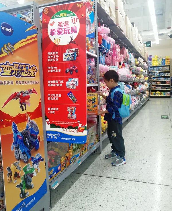 """小朋友在沃尔玛玩具货架挑选""""圣诞挚爱玩具"""""""